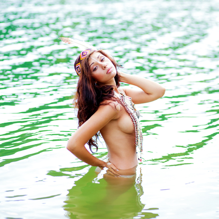 Foto de Portrait of a beautiful sexy young woman in a Native American costume posing waist-high in a river - Imagen libre de derechos