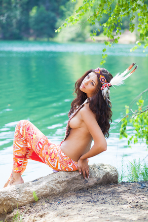 Photo pour Portrait of a beautiful sexy young woman in Indian costume posing against a forest lake - image libre de droit