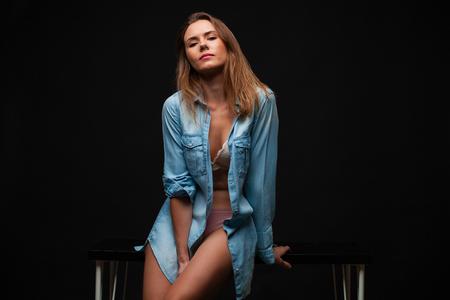 Foto de Portrait of a young sexy girl in a denim shirt and nude beautiful legs sitting on a table in a dark studio - Imagen libre de derechos
