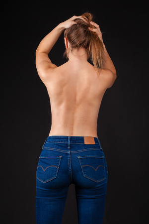 Photo for Back view, sexy young woman in denim jeans against the dark wall studio - Royalty Free Image