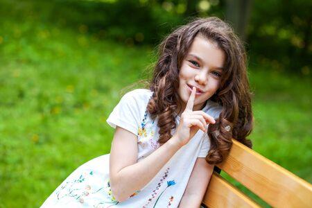 Foto für Young beautiful Little girl has put forefinger to lips as sign of silence, outdoors summer - Lizenzfreies Bild