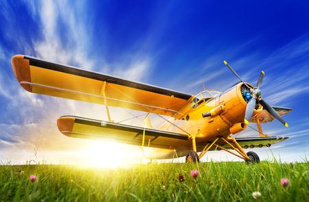 Foto de Historic biplane on a meadow against a sunset - Imagen libre de derechos