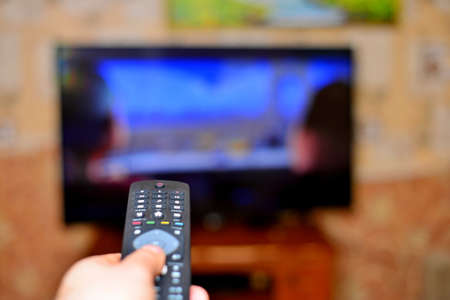 Foto de The man with the remote control in hand watching the sports channel and presses the button on the remote control. Remote control in hand closeup. - Imagen libre de derechos