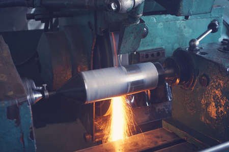 Foto de Grinding the shaft on the machine with sparks and cooling, at different angles - Imagen libre de derechos