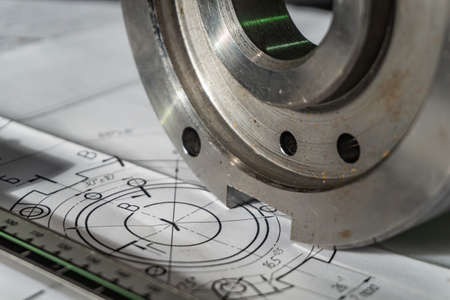 Photo pour The transition flange after processing lies on the technical drawing. Next to the part is the measuring tool, a caliper - image libre de droit