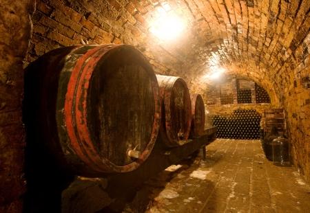 Photo pour Wine barrels vand bottles in the back in a cellar . Warm colors, wide angle view. - image libre de droit