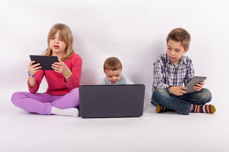 Sister and brother using tablets and their younger brother who is a baby using laptop