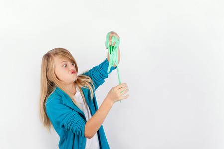 Foto de Schoolgirl playing with green slime looks like gunk - Imagen libre de derechos