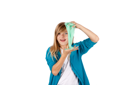 Foto de Young girl playing with slime. Isolated on white background. - Imagen libre de derechos