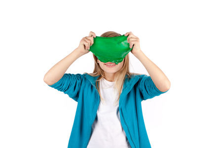 Foto de Funny girl holding a green slime looks like a disgusting thing in front of her face. Isolated on white background. - Imagen libre de derechos