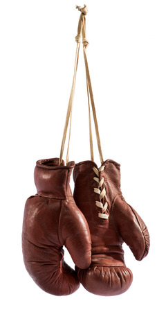 Foto de Pair of vintage brown leather boxing gloves hanging from a hook by their laces, isolated on white - Imagen libre de derechos