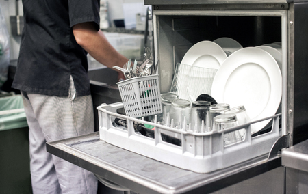 Photo pour Kitchen hand with an open dishwasher filled with clean white plates in a restaurant kitchen in a catering and hygiene concept - image libre de droit