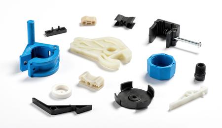 Foto de Many different injection plastic parts of white, blue and black colour spread on white background - Imagen libre de derechos