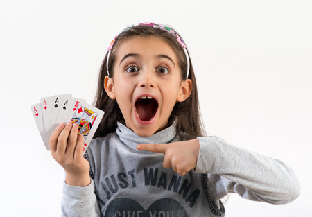 Foto de Excited little girl pointing to a winning poker hand with four aces and a king with wide eyes and her mouth open, over white - Imagen libre de derechos