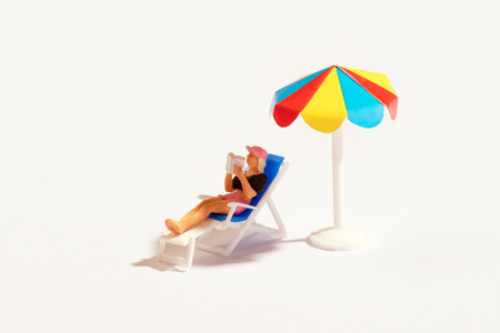 Foto de Miniature person reading a book relaxing on a recliner chair sunbathing in the shade under a colorful beach umbrella over white with copy space - Imagen libre de derechos