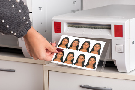 Foto de Set of just printed passport photos of a young woman exiting the printer with the hand of a woman reaching for the sheet in a close up view - Imagen libre de derechos