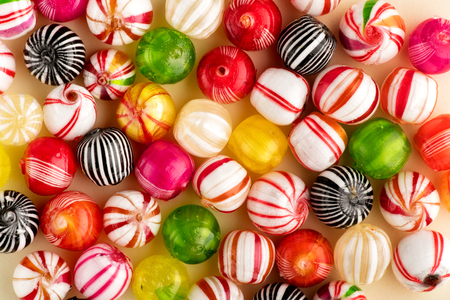 Photo for Colorful round candies of red, white, green, yellow and black colors with stripes, sitting on table surface in one layer, top view in full frame - Royalty Free Image