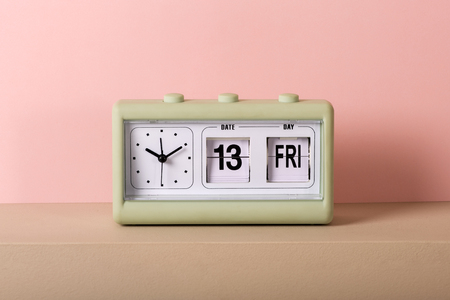 Foto de Small green vintage clock with white face and calendar showing Friday 13th. Viewed from the front in close-up, against pale pink background - Imagen libre de derechos