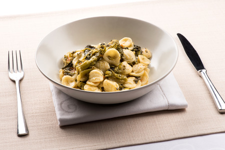 Photo for Orecchiette con Cime di Rapa, or a bowl of orecchiette pasta with broccoli rabe, a regional dish from Puglia, Italy served in a bowl at table - Royalty Free Image