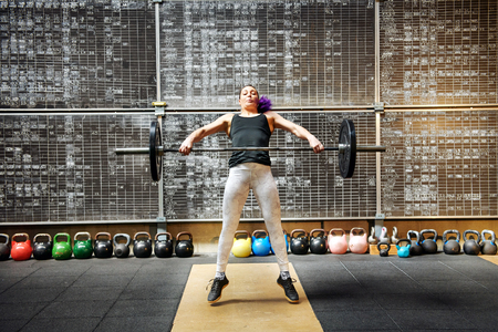 Photo for Young woman athlete doing the snatch with a barbell snatching it off the ground to lift it above her head in a single movement seen straining with effort as she raises the weight - Royalty Free Image
