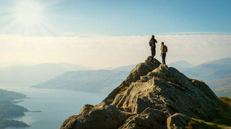 Foto de Two female hikers on top of the mountain enjoying valley view, Ben A - Imagen libre de derechos