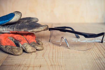 Foto de Old used safety glasses and gloves on wooden background - Imagen libre de derechos