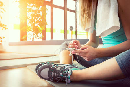Foto de Attractive blond woman with smart phone, resting after gym workout - Imagen libre de derechos