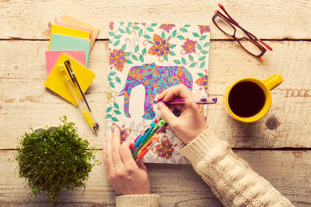 Foto de Woman coloring an adult coloring book, new stress relieving trend, mindfulness concept, hand detail - Imagen libre de derechos