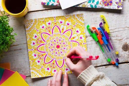 Photo pour Woman coloring an adult coloring book, new stress relieving trend, mindfulness concept, hand detail - image libre de droit