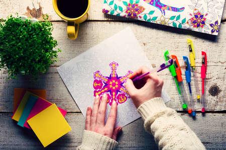 Foto de Woman coloring an adult coloring book, new stress relieving trend, mindfulness concept, hand detail - Imagen libre de derechos