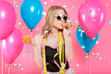 Photo for Gorgeous trendy young woman in party outfit celebrating birthday. Party mood, balloons, flying confetti, cocktail and dancing concept on pastel pink background.  - Royalty Free Image