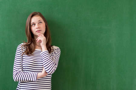 Photo for Student thinking and leaning against green chalkboard background. Pensive girl looking up. Caucasian female student portrait with copy space. Imagination, ideas, future, possibilities concept. - Royalty Free Image