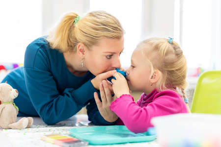 Foto de Toddler girl in child occupational therapy session doing sensory playful exercises with her therapist. - Imagen libre de derechos