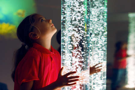 Foto de Child in therapy sensory stimulating room, snoezelen. Child interacting with colored lights bubble tube lamp during therapy session. - Imagen libre de derechos
