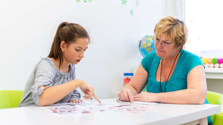Foto de Mature female therapist working with a teenage girl with learning difficulties to master logical tests. - Imagen libre de derechos