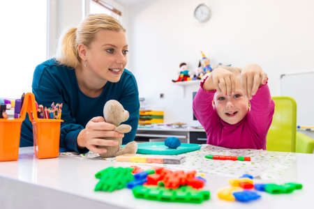 Photo pour Toddler girl in child occupational therapy session doing sensory playful exercises with her therapist. - image libre de droit