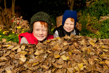 Two happy smiling brothers sit in a heap of colorful autum leaves wearing warm clothes and hats in a park or garden setting