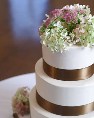 Closeup of white weding cake with brown ribbon and flowers on top.