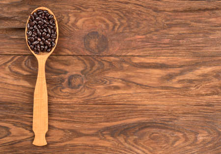 Photo for Sunflower seeds in chocolate in a spoon on an empty table, top view - Royalty Free Image