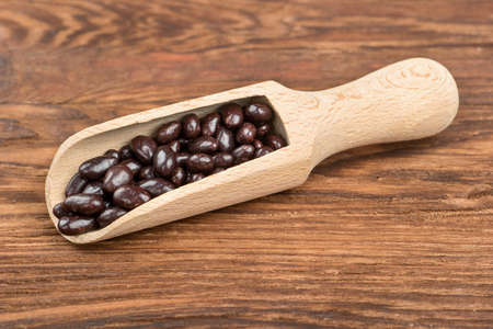 Photo for Sunflower seeds in the chocolate scoop on wooden background - Royalty Free Image