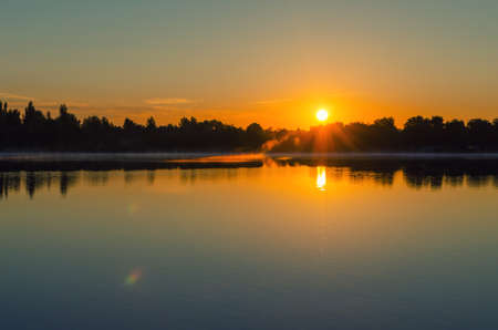 Foto de Dawn on the lake, the sun comes out of the trees. - Imagen libre de derechos