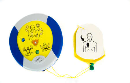 Foto de An automated external defibrillator or AED with pads isolated on white. - Imagen libre de derechos