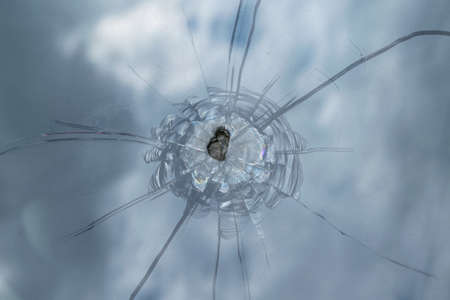 Foto de The broken windshield of the car from flying stone. The hole in the glass, chips and debris, cracks in strips. The glass reflects the sky with clouds. - Imagen libre de derechos