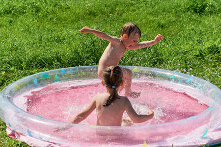 Photo pour Little boy and girl are swimming in the inflatable outdoor pool. The boy stomps his foot and splashes fly to the sides. Baby waving his hands. Girl splashing around and looking at the boy. - image libre de droit