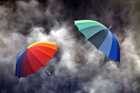 Colorful umbrella on a dark dramatic sky