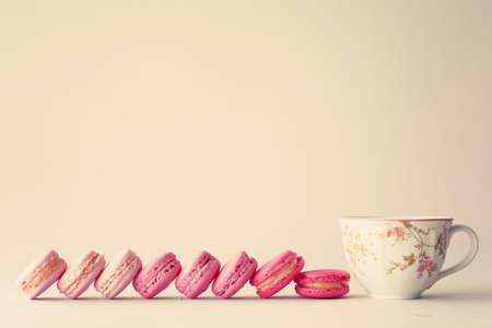 Line of macaroons and vintage tea cup