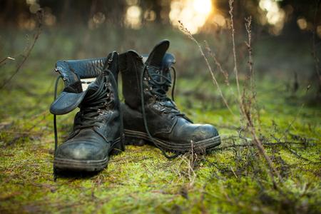 Foto de Old leather combat boots on green grass with free copy space on the left side. - Imagen libre de derechos