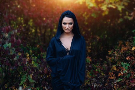 Photo for A girl in a black dress, a cloak with a hood. It stands against the background of the autumn forest. Witch Costume, Satanist, Necromancer, Halloween Costume - Royalty Free Image