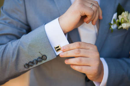 Foto de close-up of elegance male hands. man dressed in blue suit and white shirt standing over green nature background. groom in wedding day - Imagen libre de derechos