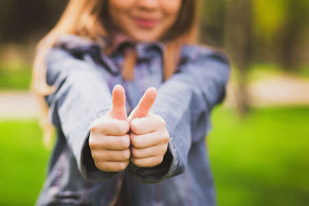 Photo pour Young girl puts her big thumbs up. Portrait of cheerful kid. Smiling girl having fun outside. Happy successful person. - image libre de droit